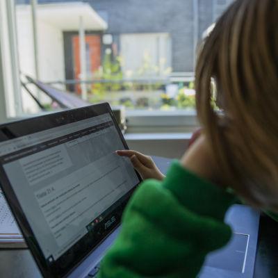 Lapsi käy etäkoulua tietokoneen avulla.