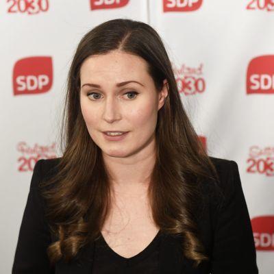SDP:s Sanna Marin. Hon står framför ett lakan med texten SDP.