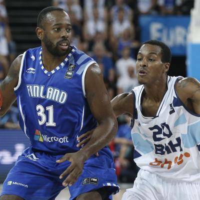 Basketspelare skyddar boll.