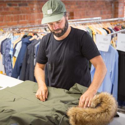 Makian suunnittelija Jesse Hyväri tutkii takkia.