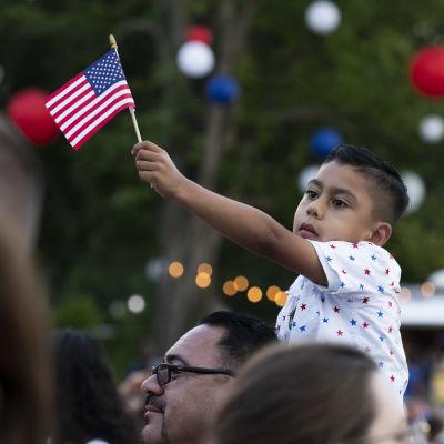En pojke viftar med USA:s flagga.
