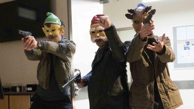 Tre män med masker som föreställer en julgubbe, tomte och en ren rusar in genom en dörr med dragna vapen.