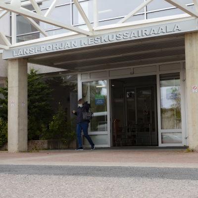 Kemin Länsi-Pohjan Keskussairaalan etuovi. Ihminen kävelee Ulos