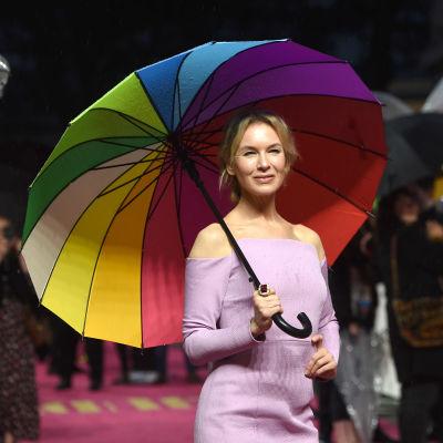 En kvinna i en ljuslila klänning håller i ett paraply i många färger.