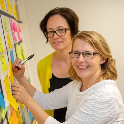 Anne Hyvärilä ja Eija Moisala seisovat kanban-taulun äärellä.