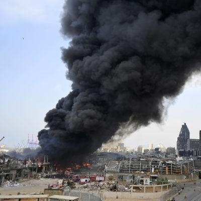 Musta savupatsas nousee satama-alueelta.