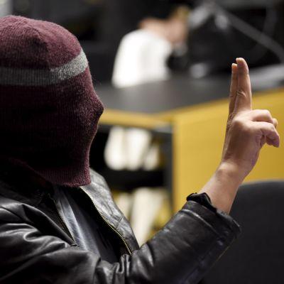 En man i skinnjacka och en mössa som är dragen ner över ansiktet gör en gest med handen.