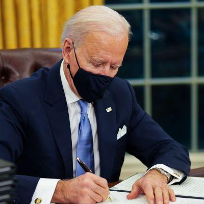 Joe Biden sitter vid skrivbordet i Ovala rummet och undertecknar dekret.