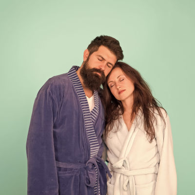 Man och kvinna båda iklädda morgontockar lutar sig mot varandra och blundar