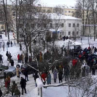 En folksamling utanför en polisstation.