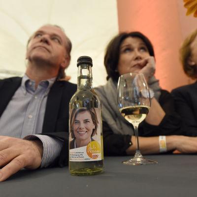 CDU-anhängare reagerar på valresultatet i Tyskland. Supportrarna sitter bakom en vinflaksa med en bild på en av CDU-kandidaterna Julia Kloeckner.