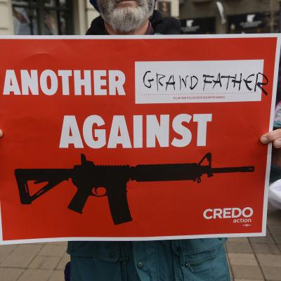 En man håller upp en skylt med texten, En till morfar mot vapen, för att protestera mot liberala vapenlagar i USA.
