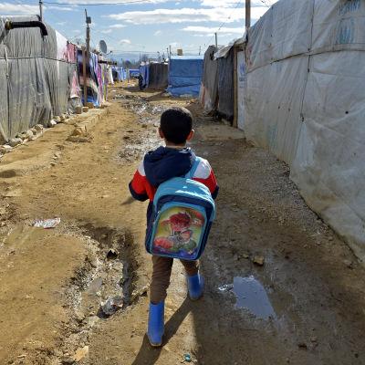 Ett syriskt flyktingbarn med blå ryggsäck promenerar i ett flyktingläger med tält i Libanon mit skolan.