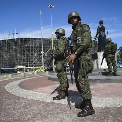 Brasilianska beväpnade soldater står utanför strandvolleybollarenan på Copacabana i Rio de Janeiro.