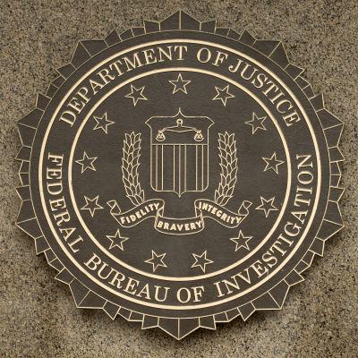 Den amerikanska federala polisen FBI:s vapen mot en grå vägg.
