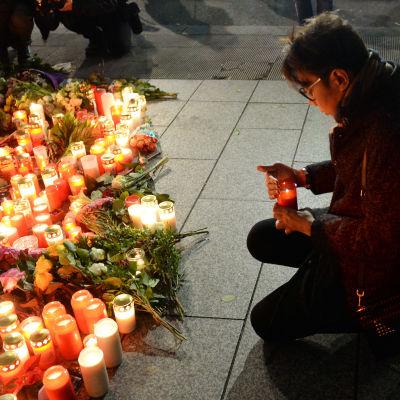 En ung man tänder ett ljus till minnet av terroroffren i Berlin. mannen håller på att lägga ner ljuset vid ett hav av blommor och ljus som lämnats av andra Berlinbor.