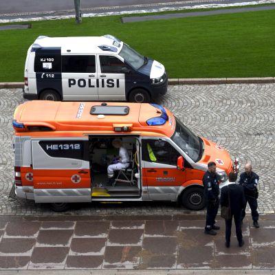 Ambulans och polisbil utanför riksdagshuset.
