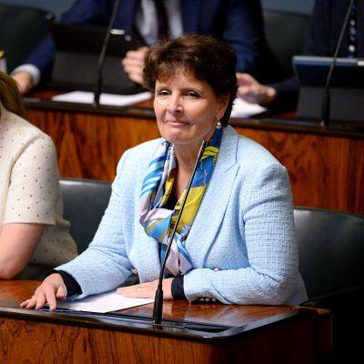 Trafikminister Anne Berner sitter i riksdagsbänken klädd i en ljusblå kavaj.
