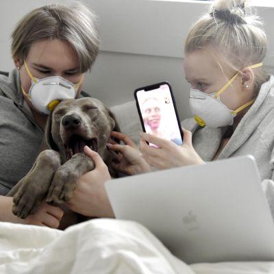 Bildsättningsbild - ungdomar med munskydd hemma tillsammans med en gäspande hund.