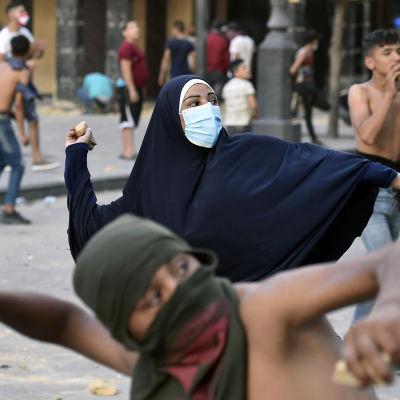 Mielenosoittajat heittivät kiviä Beirutissa 11. elokuuta 2020.
