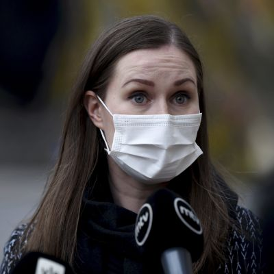 Mörkhårig kvinna i munskydd mot en brokig, diffus bakgrund. Statsminister Sanna Marin på väg till regeringens överläggning i Ständerhuset om coronaläget.