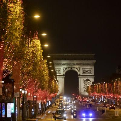 Bild på Triumfbågen i Paris. På Champs-Elysées kör bilar. Gatan omges av julljus i träden.
