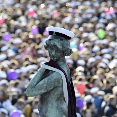 Statyn Havis Amanda iklädd en vit studentmössa. I bakgrunden syns ett vimmel av människor.