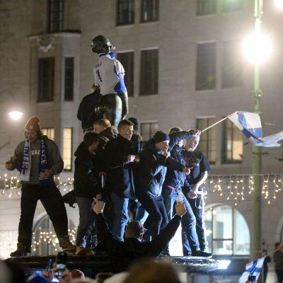 Havis Amanda iklädd landslagströja och fans som står på statyn med en flagga och firar.