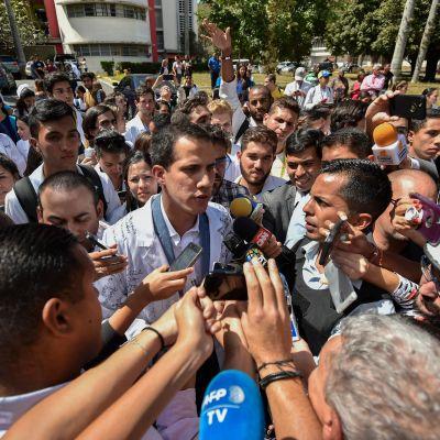 Oppositionsledaren Juan Guaidó talade med reportrar medan han deltog i onsdagens protester utanför universitetet i Caracas.