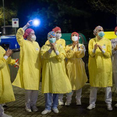 En grupp skyddsklädda sjukskötare i Barcelona vinkar åt människor som samlats på sina balkonger för att hedra dem.