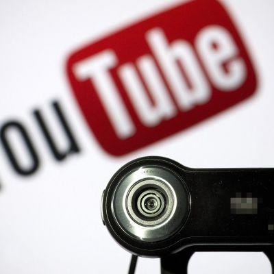 En webbkamera. I bakgrunden syns Youtubes logo.