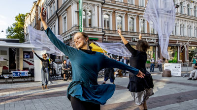 Dansare på gågatan i Åbo rör sig graciöst med vita skynken i händerna.