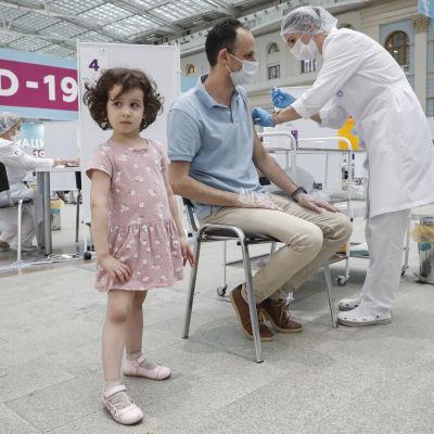 En sittande man får coronavaccin på en klinik, hans lilla dotter står bredvid.