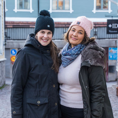 Två glada unga kvinnor iklädda mössa står bland gamla hus