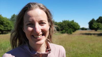 Charlotta Berlin, en dam med rosa jacka och ljust hår, står på en sommaräng.