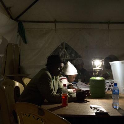Valfunktionärer räknar röster i Kibera under natten till onsdagen.