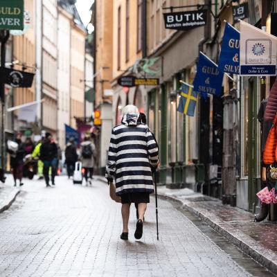 Kvinna i randig kappa går i gamlastan i Stockholm. Gatan är folktom och kvinnan går med ryggen mot kameran.