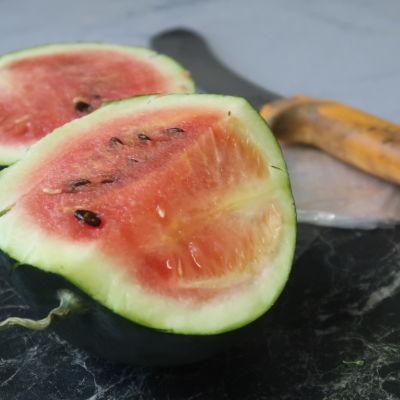 En liten uppskuren vattenmelon på ett bord, en kniv i bakgrunden.
