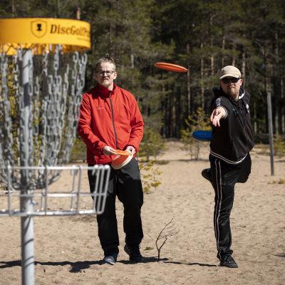 Vasemmalla frisbeegolfkori ja oikealla kaksi frisbeegolfaajaa. Frisbee lentää ilmassa kohti koria.