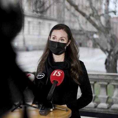Statsminister Sanna Marin (SDP) i svart munskydd vid Ständerhusets trappor. Hon talar i mikrofoner som ställts framför henne.