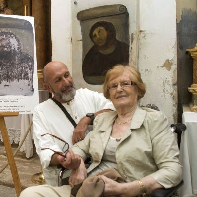 Ecce Homo -freskon pilannut rouva Cecilia Gimenez (edessä) on noussut kuuluisuuteen ja hänen tarinastaan on tehty jopa ooppera. Vieressä teatteriohjaaja Andrew Flack. Taustalla rouva Gimenezin parantelema fresko.