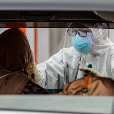 En person som sitter i en bil testas för coronaviruset av en vårdare klädd i skyddsutrustning.
