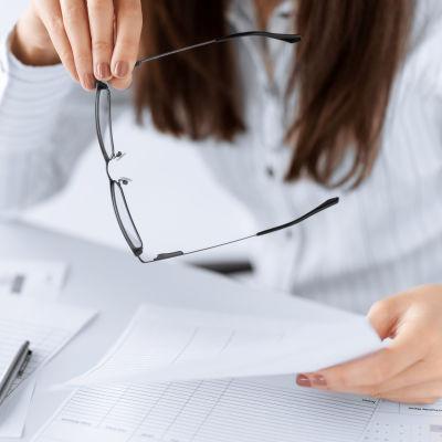 Kvinna håller i sina glasögon och ett tomt formulär.