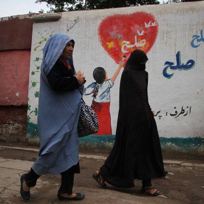 Afgaaninaiset kävelevät graffititaiteen ohitse.
