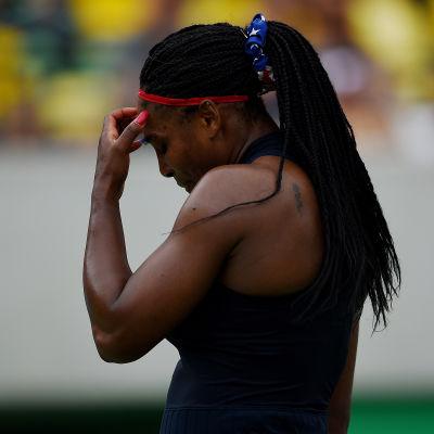 Kvinnlig tennisspelare tar sig för pannan.