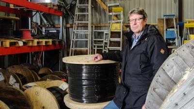 En man i ytterjacka står i en industrihall bredvid två stora kabelrullar.