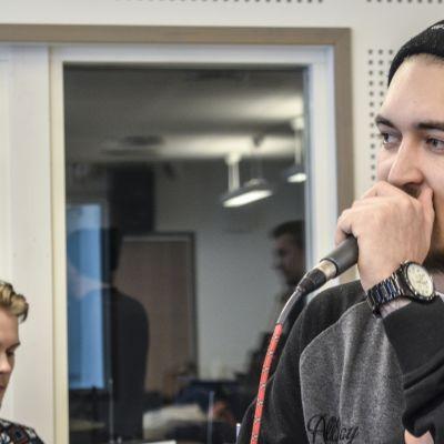 Kaksi nuorta miestä, joista toinen soittaa rumpuja ja toinen räppää mikrofoniin.