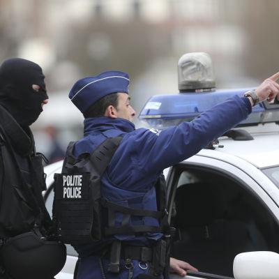 Säkerhetsstyrkor under en polisräd i Forest i Bryssel 15.3.2016.