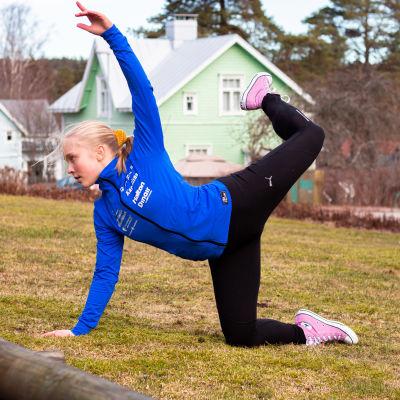 En ung kvinna med blå sportjacka gör en gymnastisk rörelse på en gräsmatta.Ett ben och ena armen i luften. de andra mot marken. Hus i bakgrunden