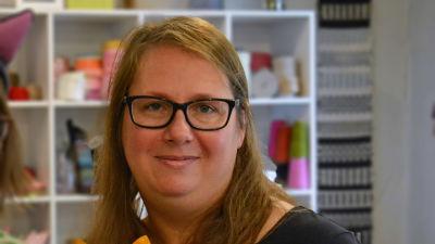 En kvinna med långt brunt hår och glasögon